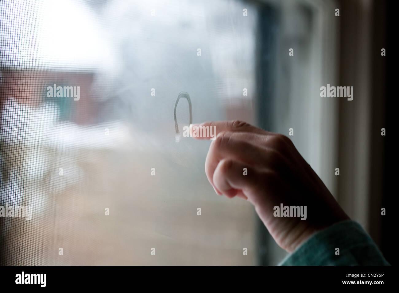 Dessin de fille de la condensation sur la fenêtre Photo Stock
