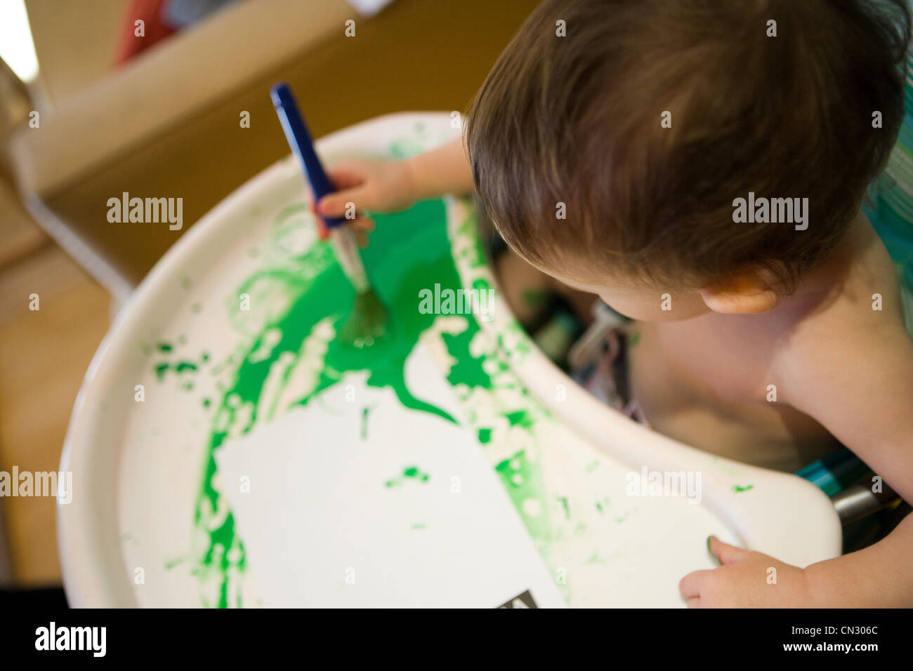 Baby Boy in chaise haute avec la peinture verte Photo Stock