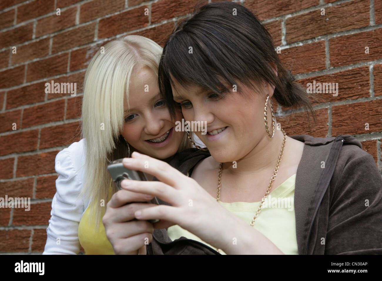 Deux jeunes femmes looking at mobile phone Photo Stock