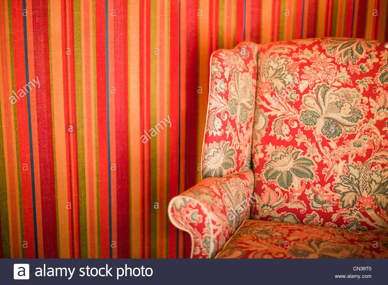 Fauteuil à motifs floraux contre mur rayé Photo Stock