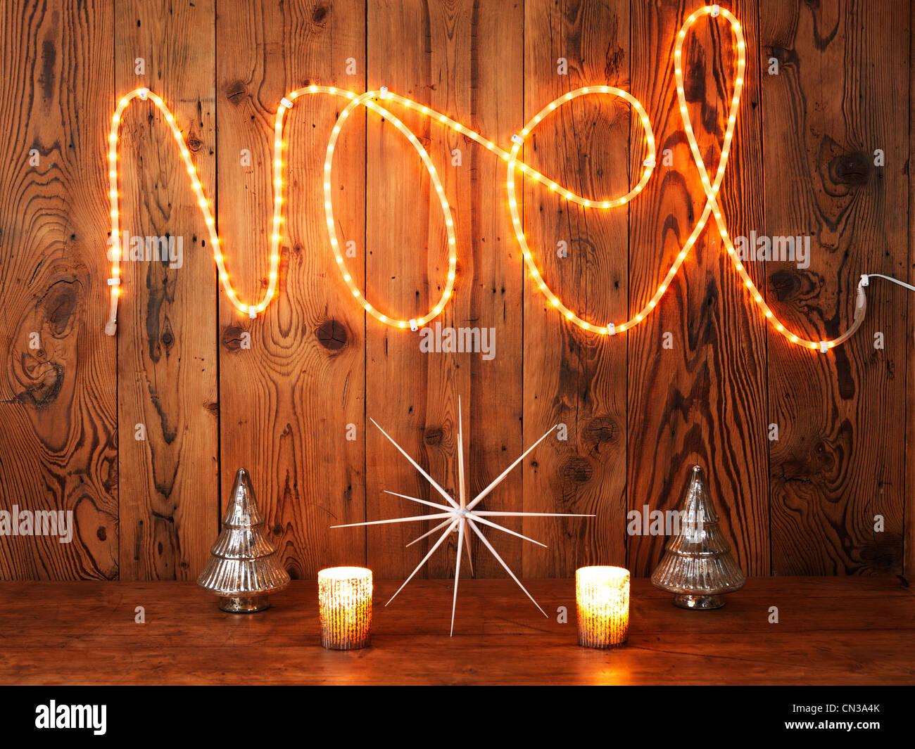 Les lumières de Noël l'orthographe Noel contre les boiseries Photo Stock