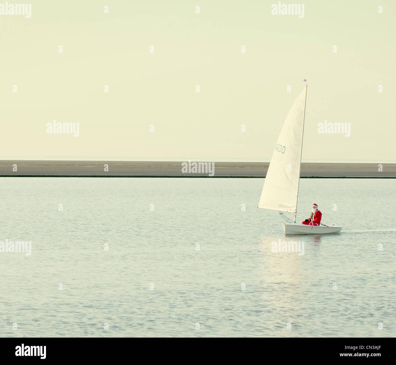 Personne habillé en père Noël en bateau sur le lac Photo Stock