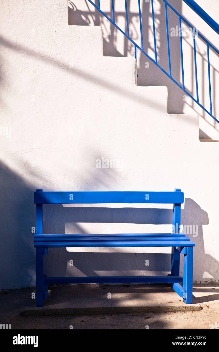 Banc en bois bleu traditionnel contre mur blanchis au soleil à Skiathos, Grèce Banque D'Images