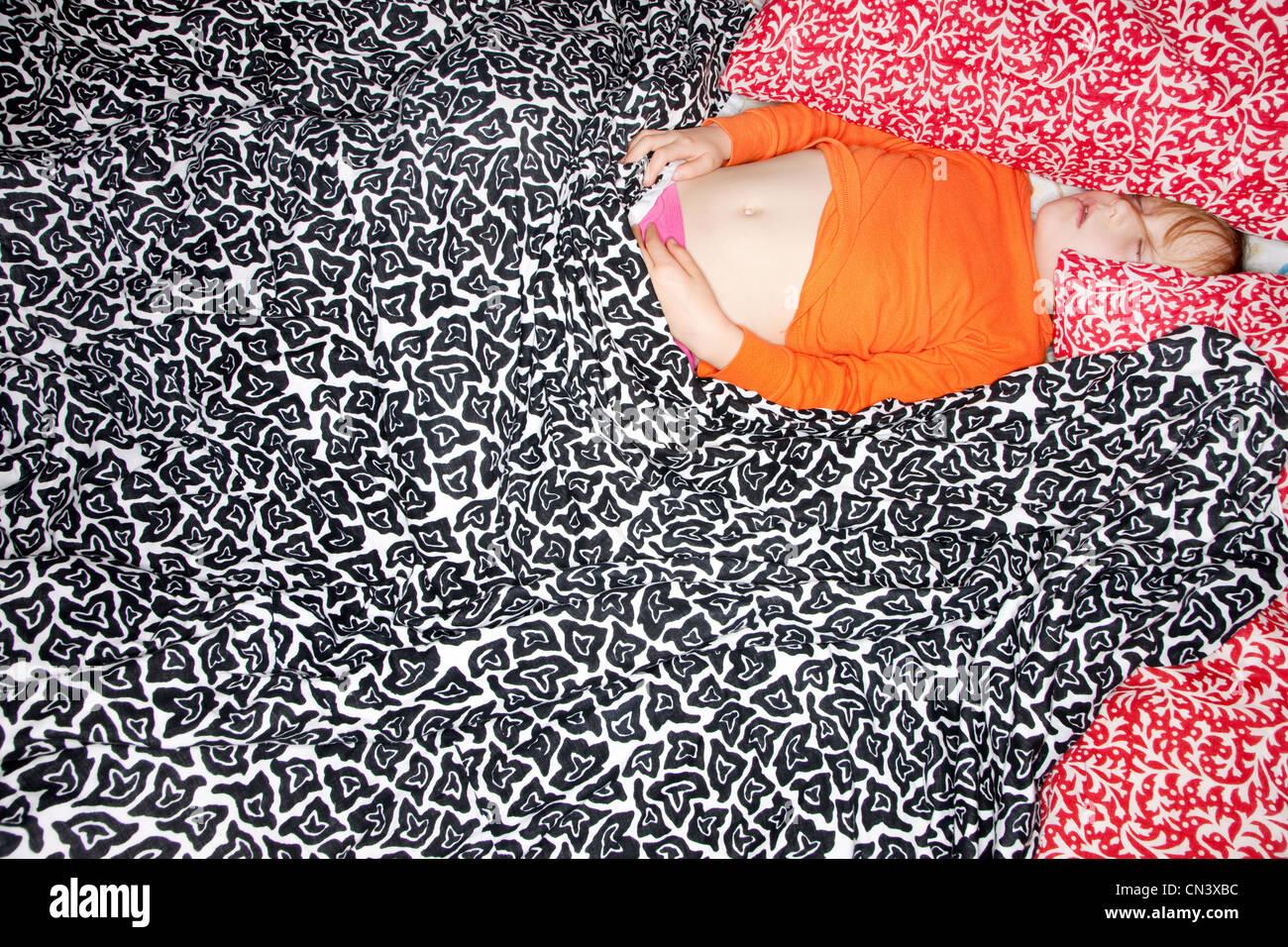 Fille de dormir dans des draps à motifs Photo Stock