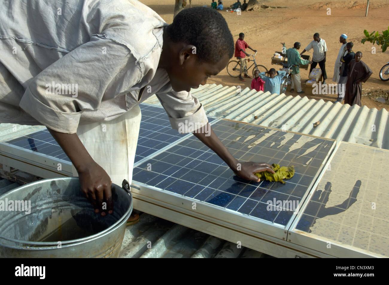 Jeune garçon nettoie la poussière de panneaux solaires en Afrique Photo Stock