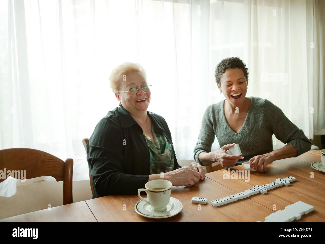 Mère et fille adultes jouant aux dominos Photo Stock