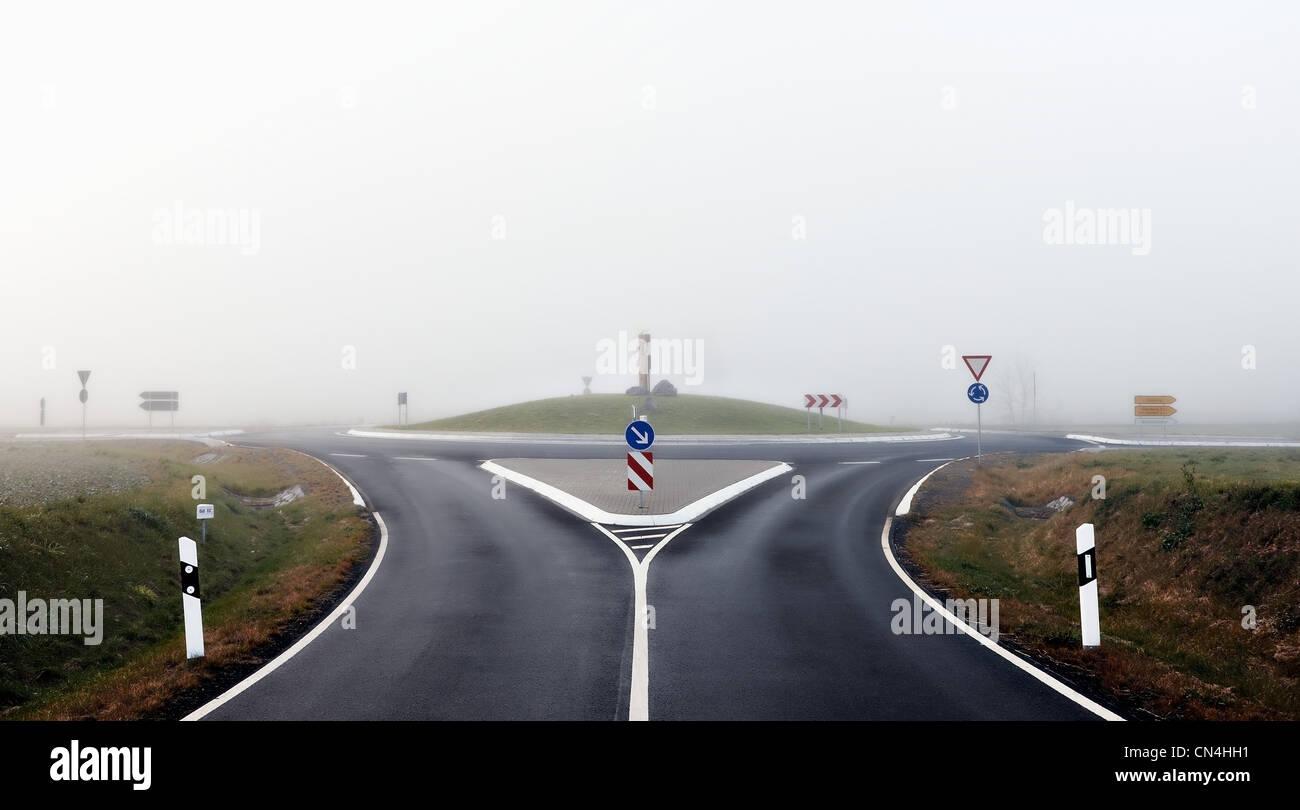 Rond-point et la route avec des signes dans la brume Photo Stock