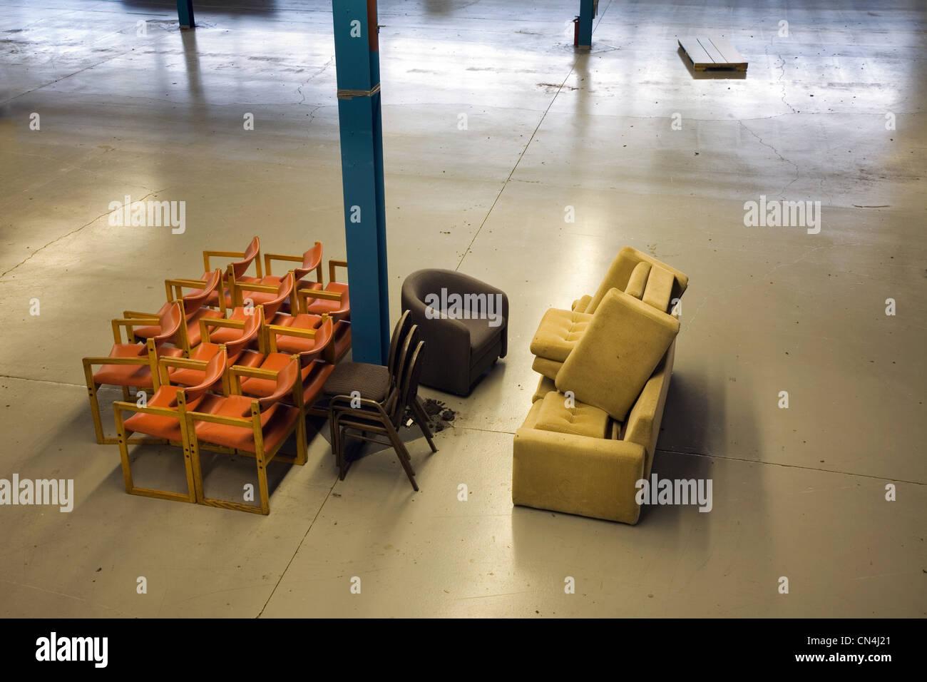 Chaises empilées dans un entrepôt vide Banque D'Images