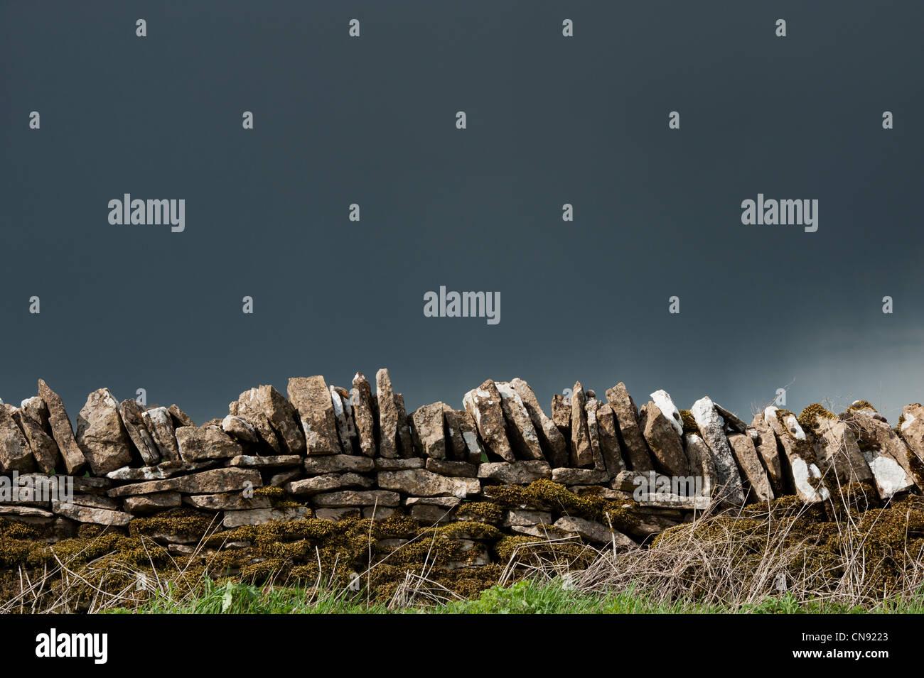 Pluie nuages orageux sur vieux mur de pierres sèches dans la campagne anglaise Photo Stock