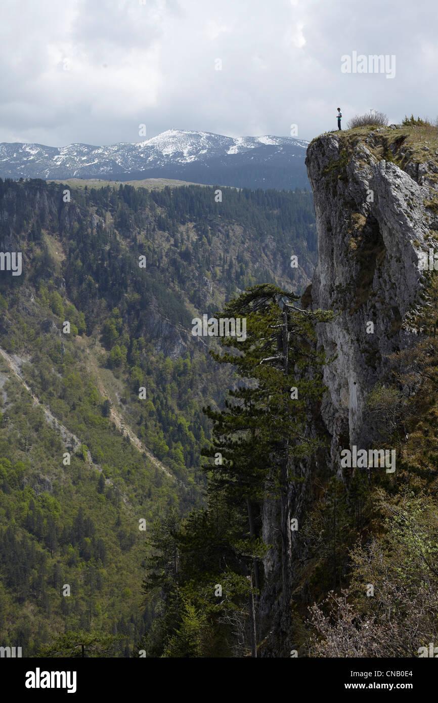 Homme debout sur une falaise rocheuse Photo Stock