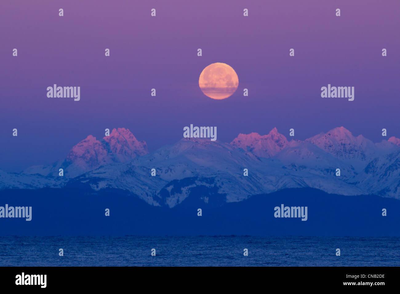 Réglage de pleine lune derrière les montagnes Chilkat et Canal Lynn au lever du soleil, le passage de Photo Stock