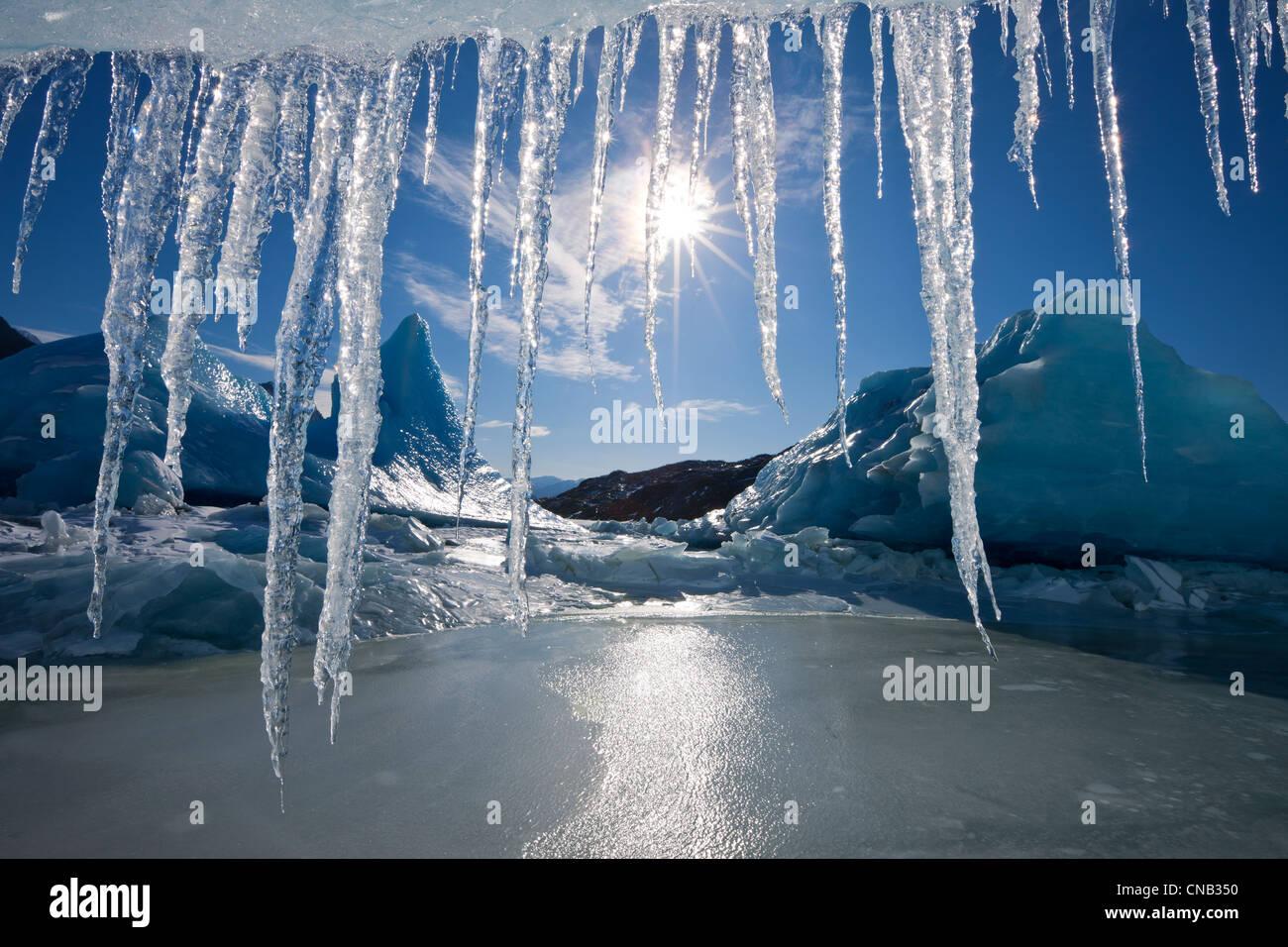 Soleil brille à travers les glaçons suspendus au bord d'un iceberg dans la surface gelée du lac Photo Stock