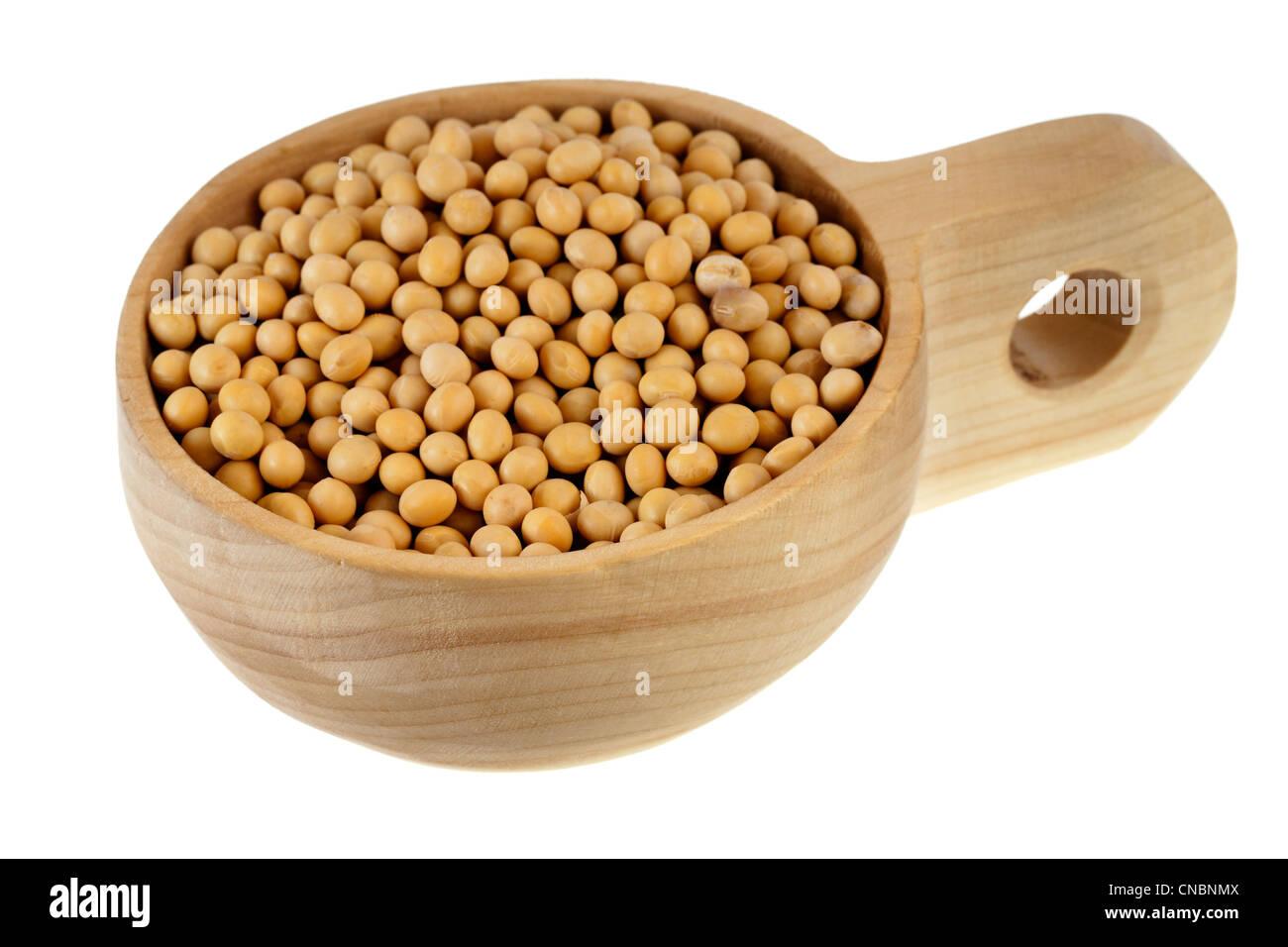 Les fèves de soja jaune sur un sol en bois, rustique, scoop ou bol, isolé sur fond blanc Photo Stock