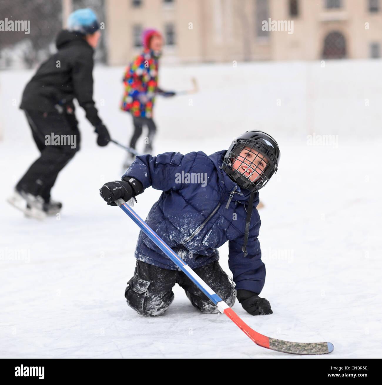Les jeunes garçons jouer au hockey sur glace sur une patinoire extérieure, Winnipeg, Manitoba, Canada Photo Stock