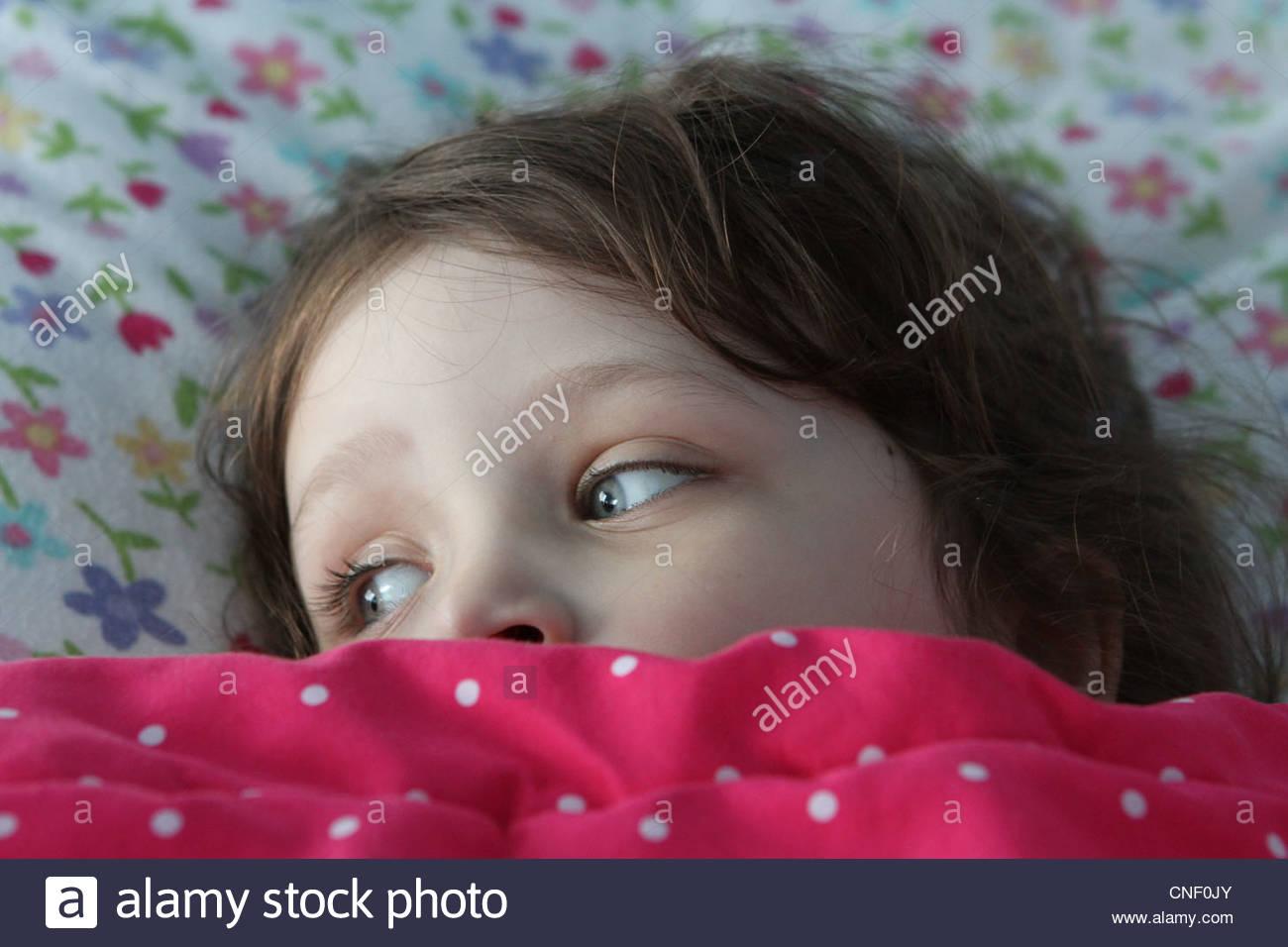Un petit enfant au lit avec des couvertures sont arrêtés dans les yeux. Banque D'Images