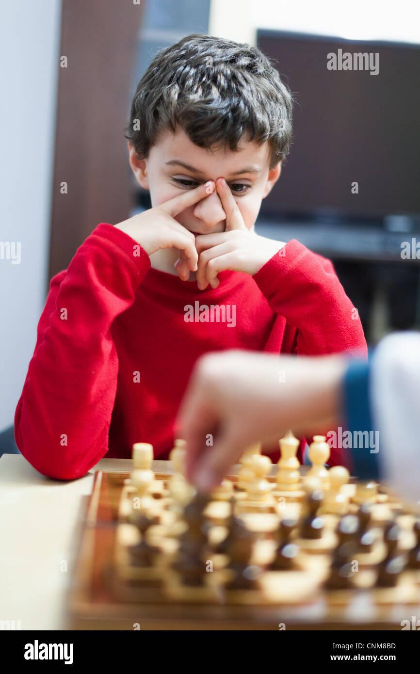 Closeup portrait of a school boy jouant aux échecs, selective focus Banque D'Images