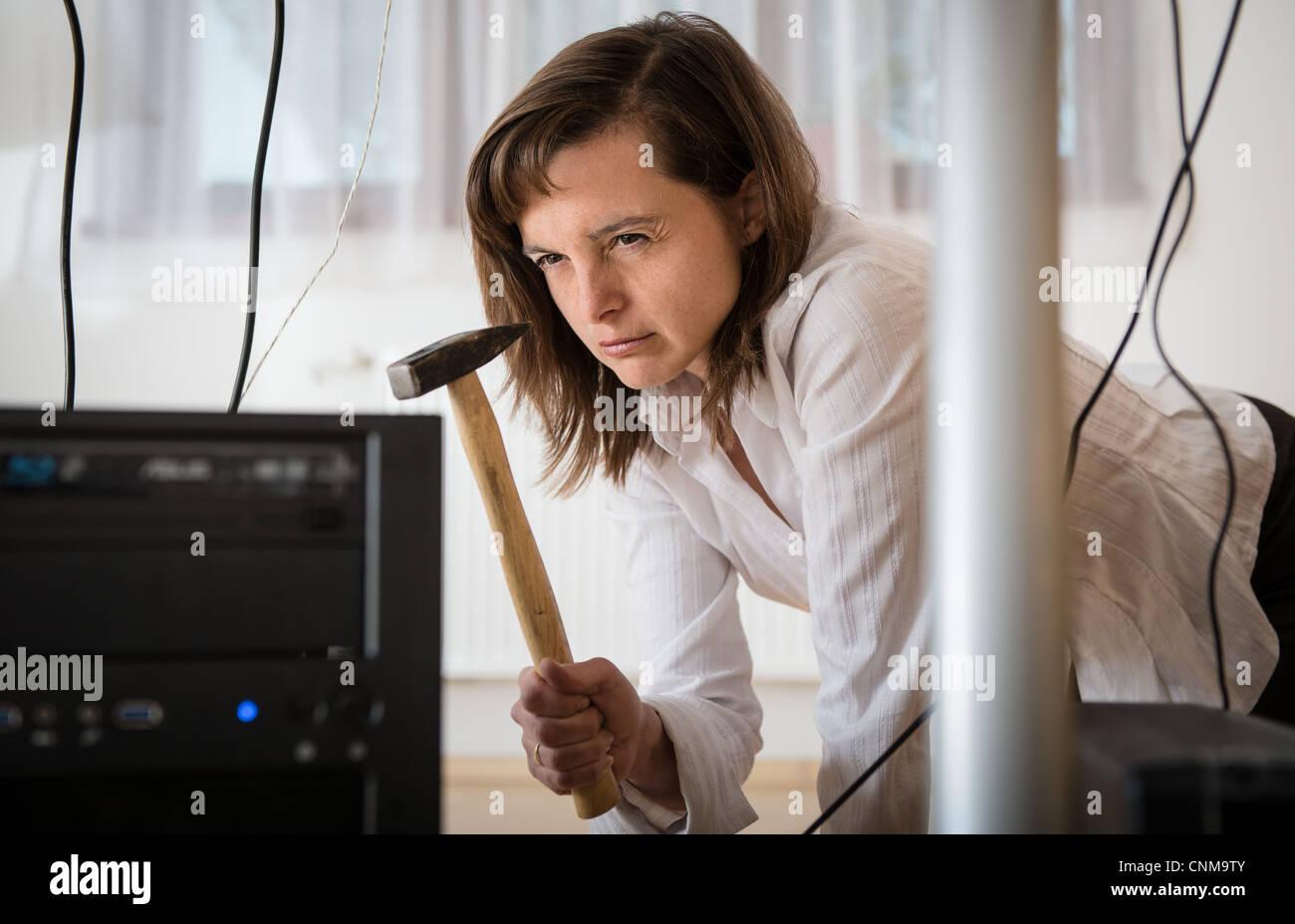 Jeune femme d'affaires ayant problème avec ordinateur et essayer de le récupérer avec un marteau Banque D'Images