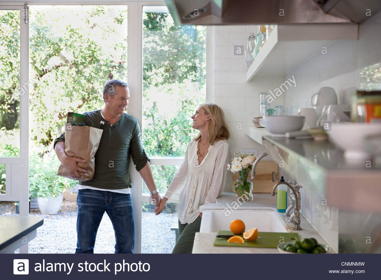 Couple holding hands in kitchen Photo Stock