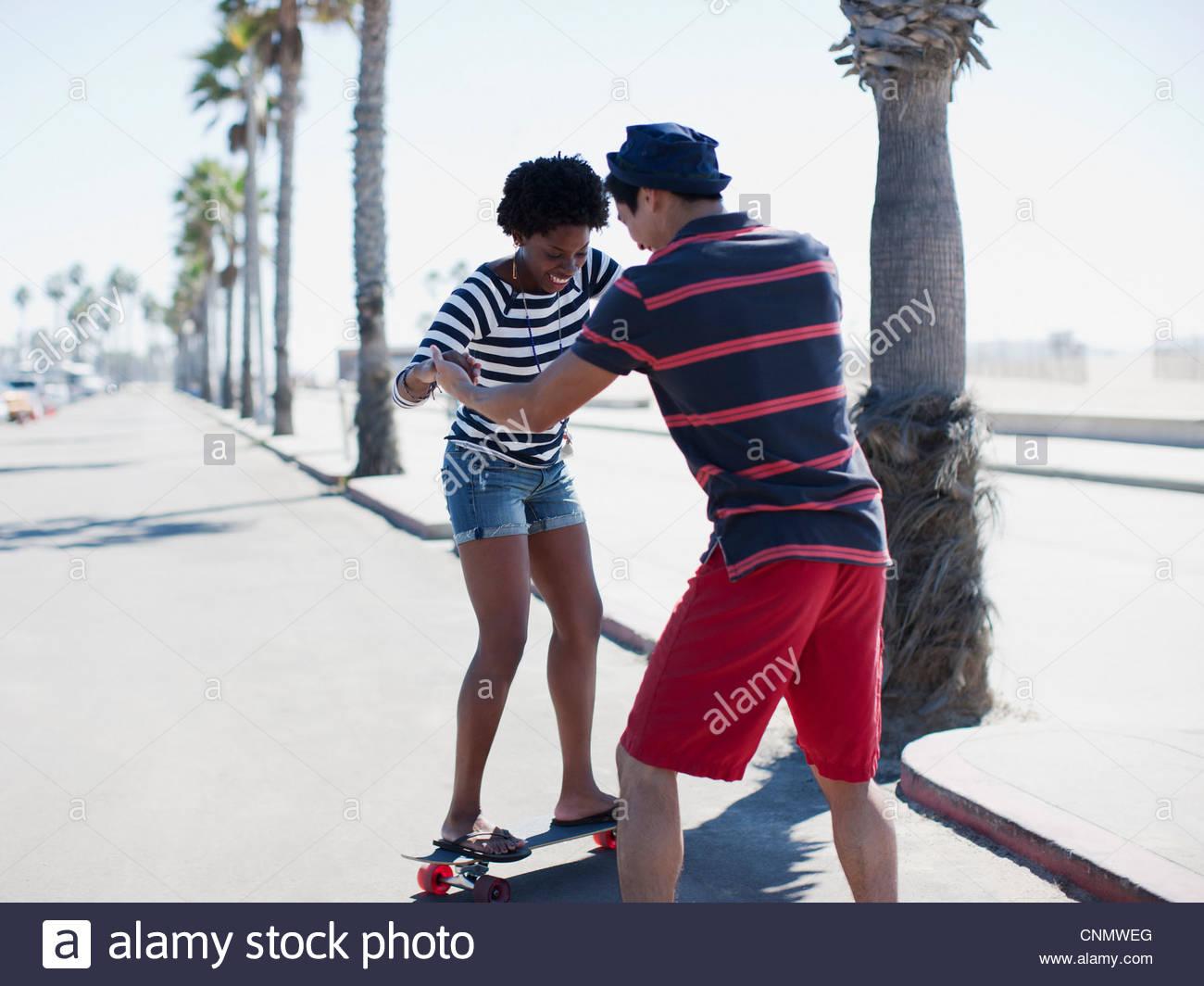 L'enseignement de l'homme petite amie à skateboard Photo Stock