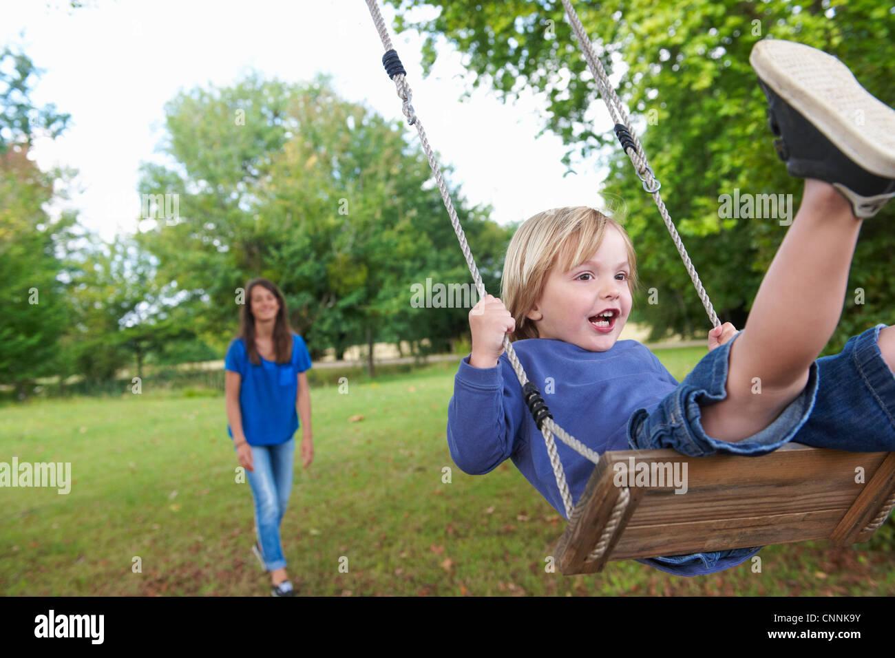 Garçon jouant sur swing in backyard Banque D'Images