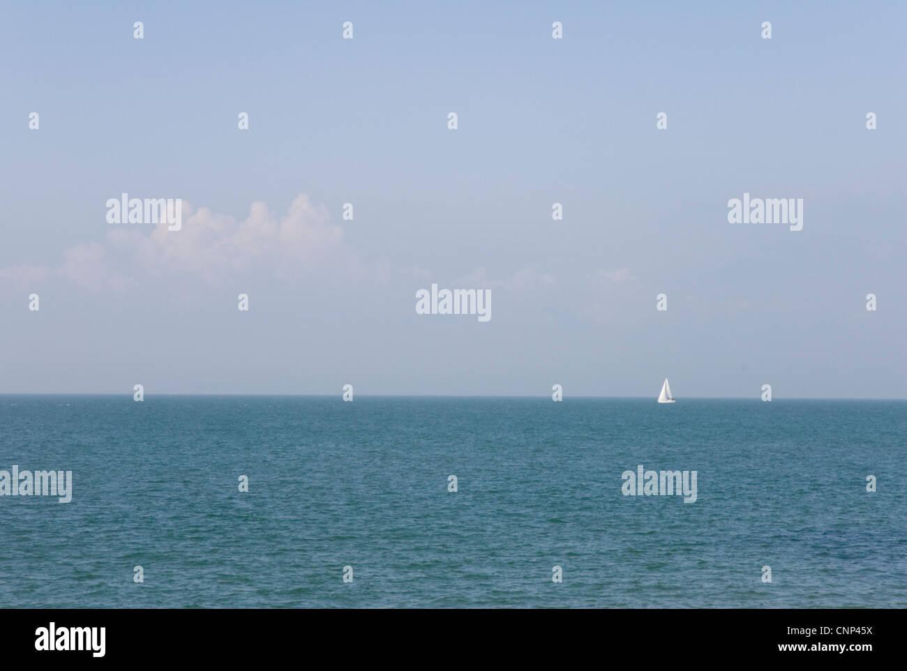 La mer bleu/vert - bleu ciel - un nuage blanc - un seul Niveau voile blanche sur l'horizon Photo Stock