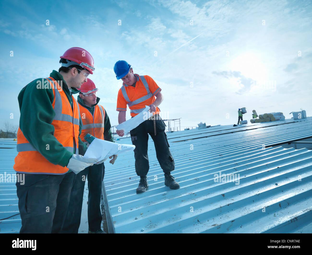 La lecture de bleus travailleurs sur le toit Photo Stock