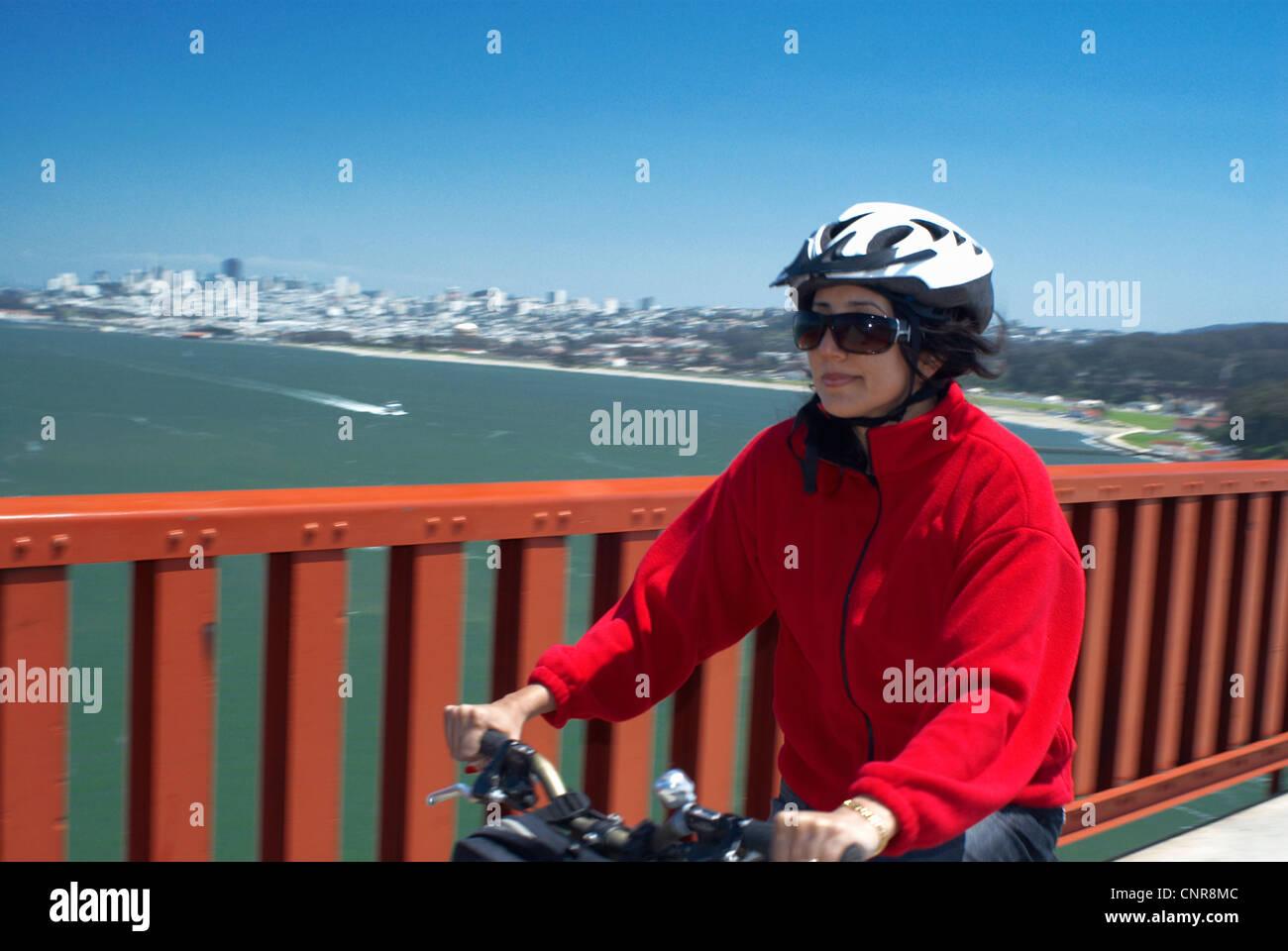 Woman riding bike sur pont urbain Banque D'Images