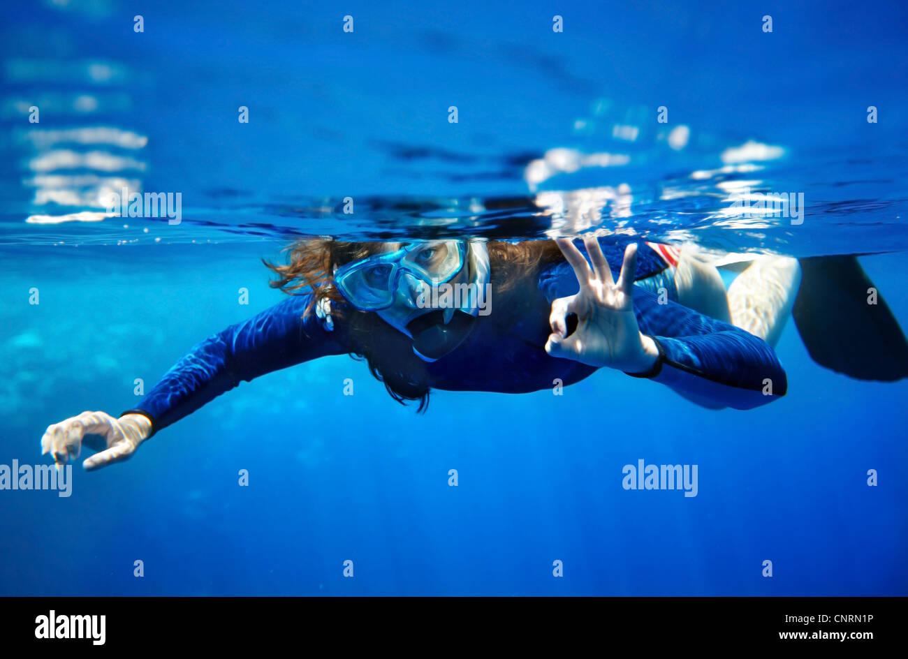 Scuba Diver jeune femme en bleu de l'eau. Photo Stock