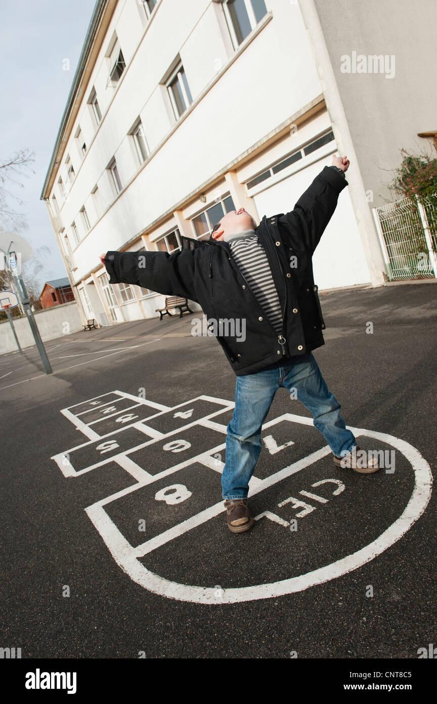 Garçon jouant à la marelle, d'inclinaison Banque D'Images