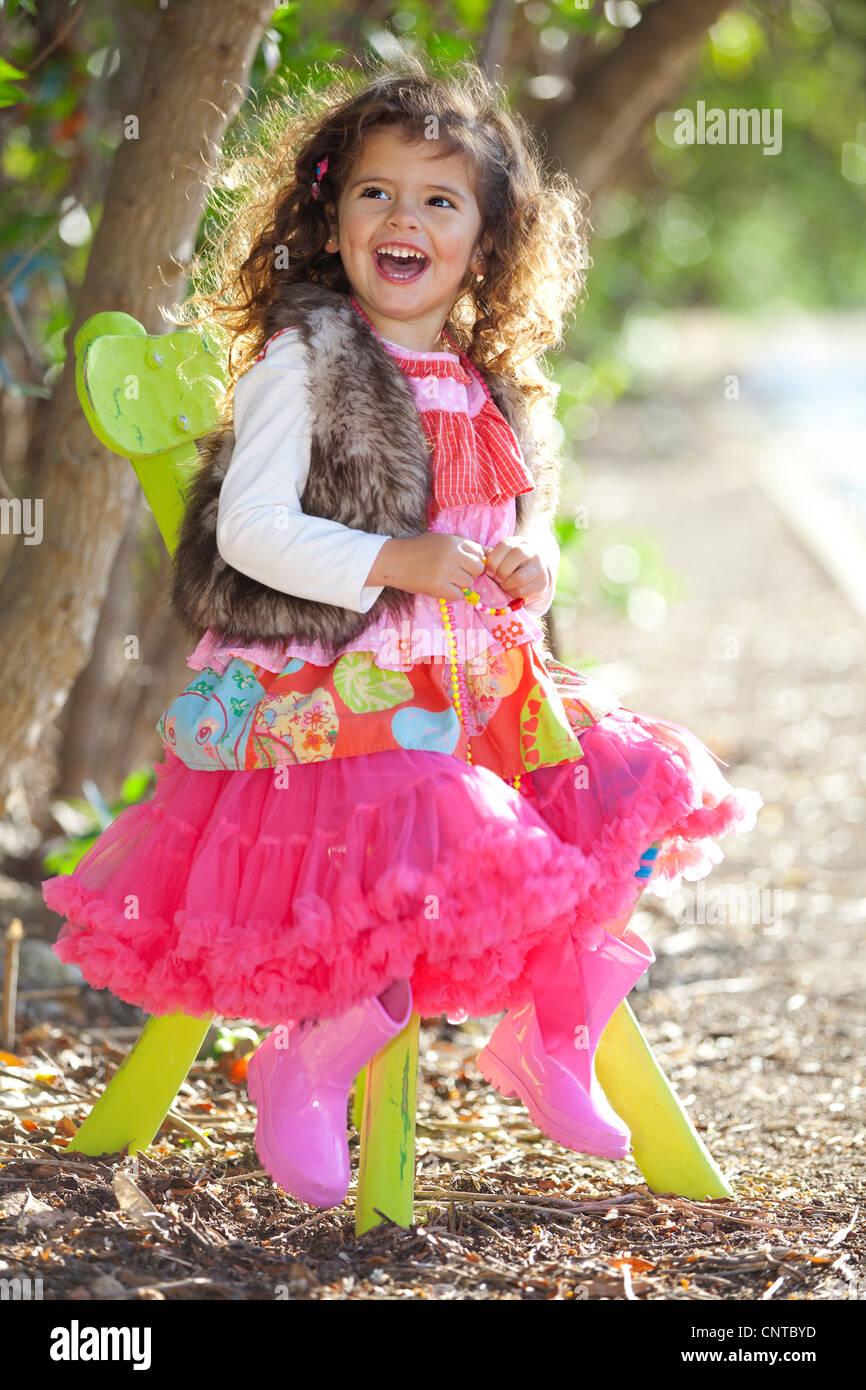 Happy smiling little girl dans des vêtements colorés assis à l'extérieur en fauteuil Photo Stock