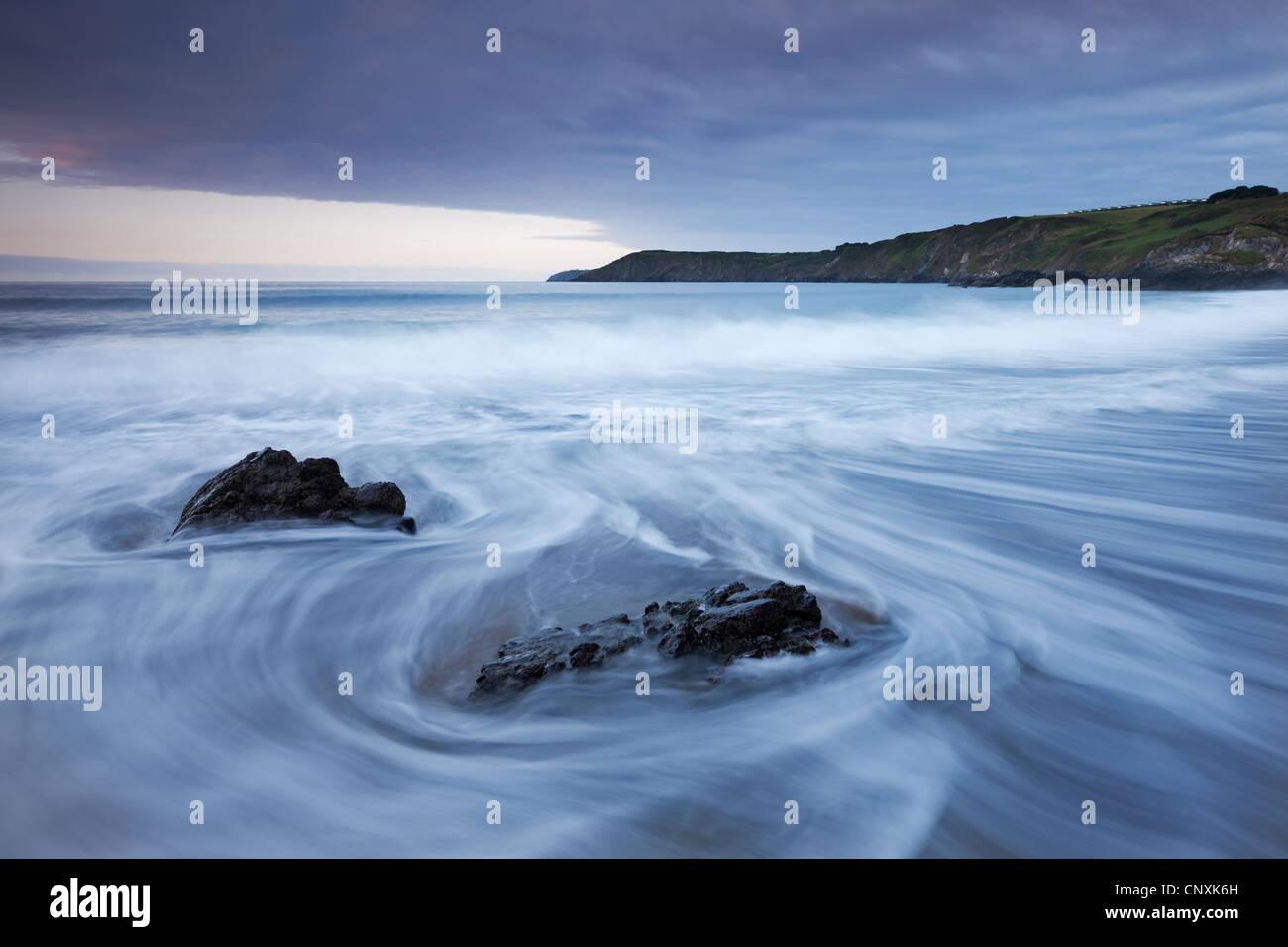 Rush des vagues sur la plage au sable, Péninsule du Lézard Kennack, Cornwall, Angleterre. Printemps (mai) Photo Stock