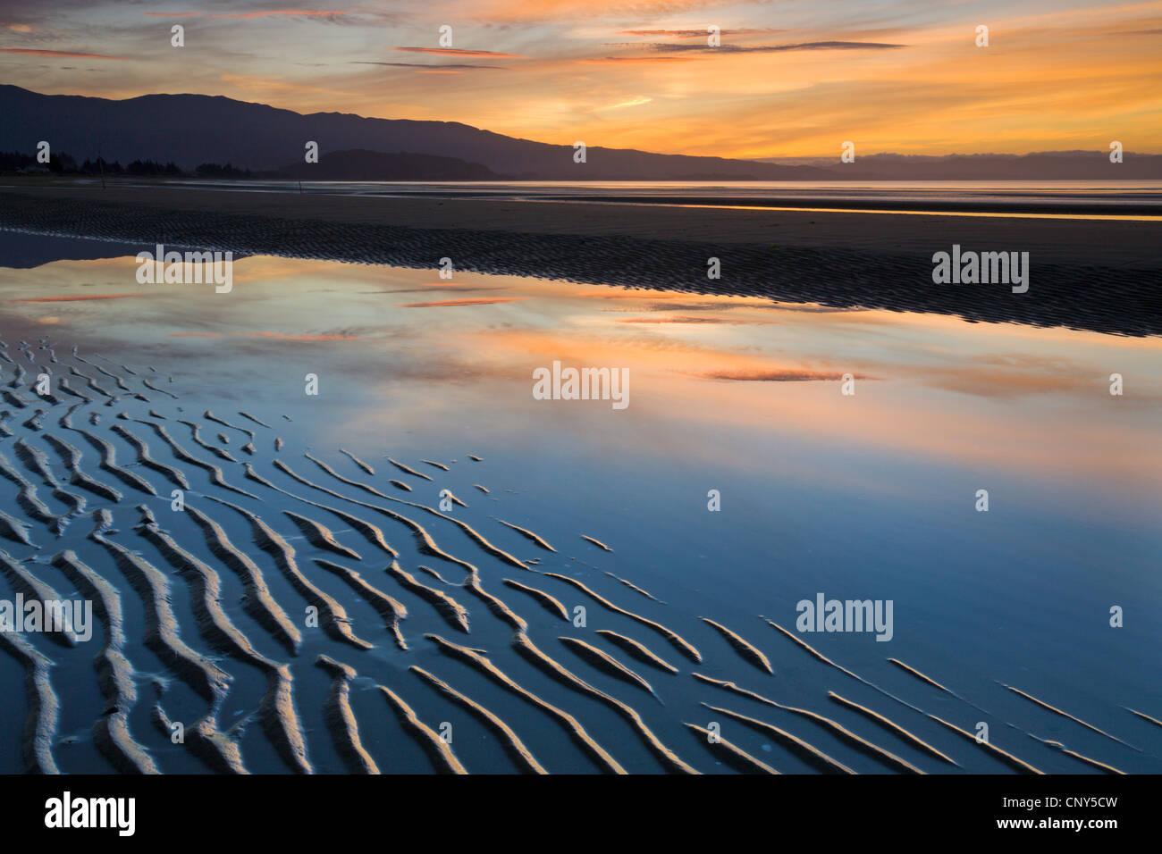 Des vagues de sable sur Pakawau Beach au coucher du soleil, Golden Bay, île du Sud, Nouvelle-Zélande. Photo Stock