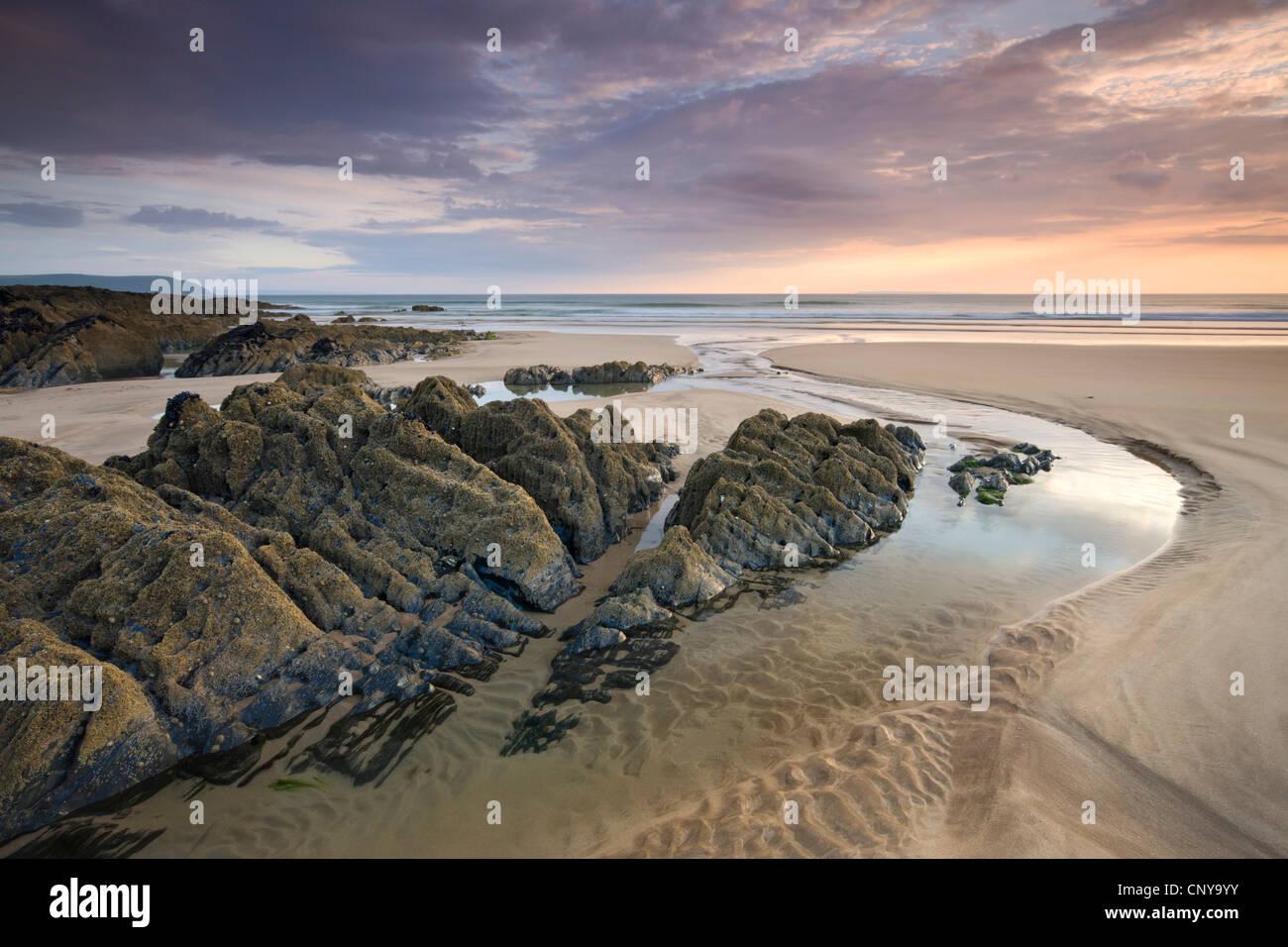 Coucher du soleil sur la plage de sable et rochers, Combesgate à Woolacombe, Devon, Angleterre. En été Photo Stock