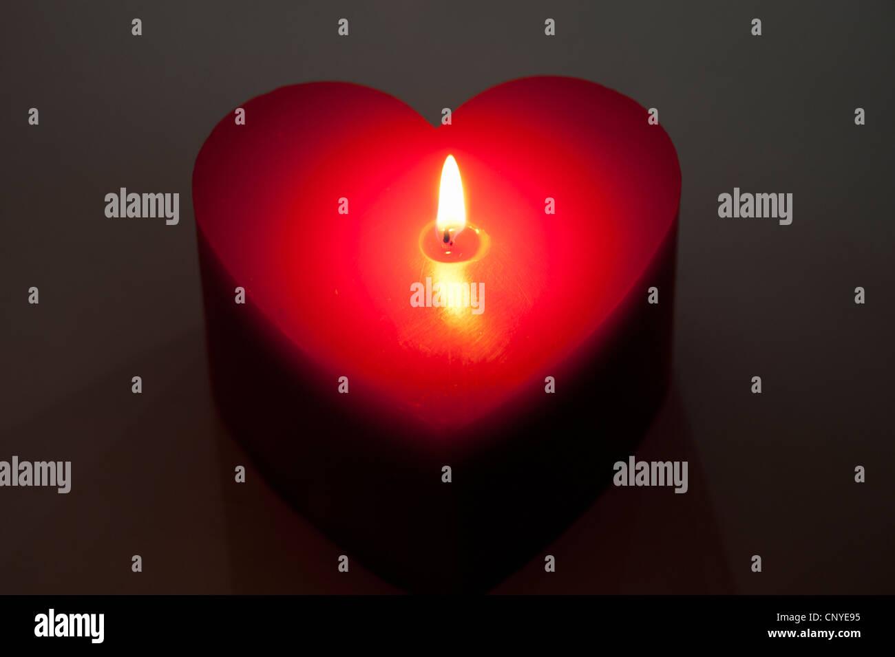 Une bougie en forme de coeur rouge, allumé Photo Stock