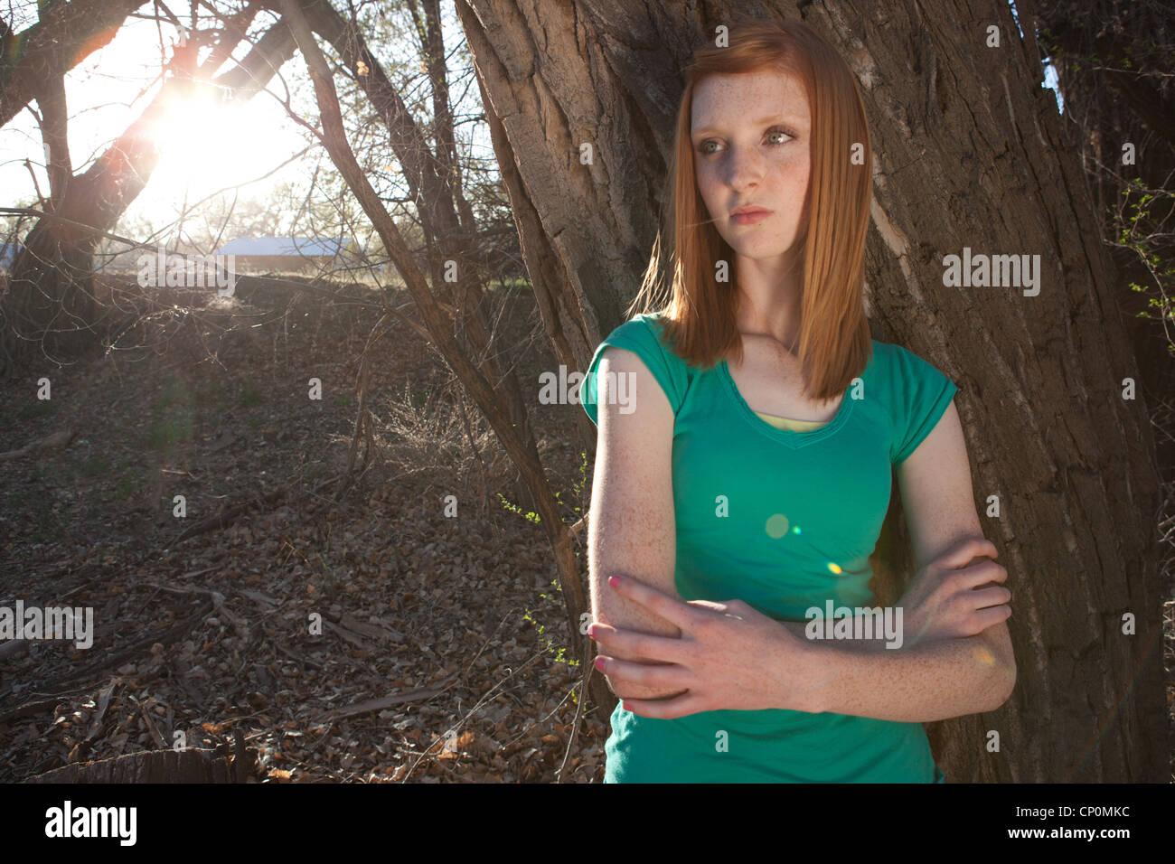Quinze ans, fille, debout près d'un arbre. Photo Stock