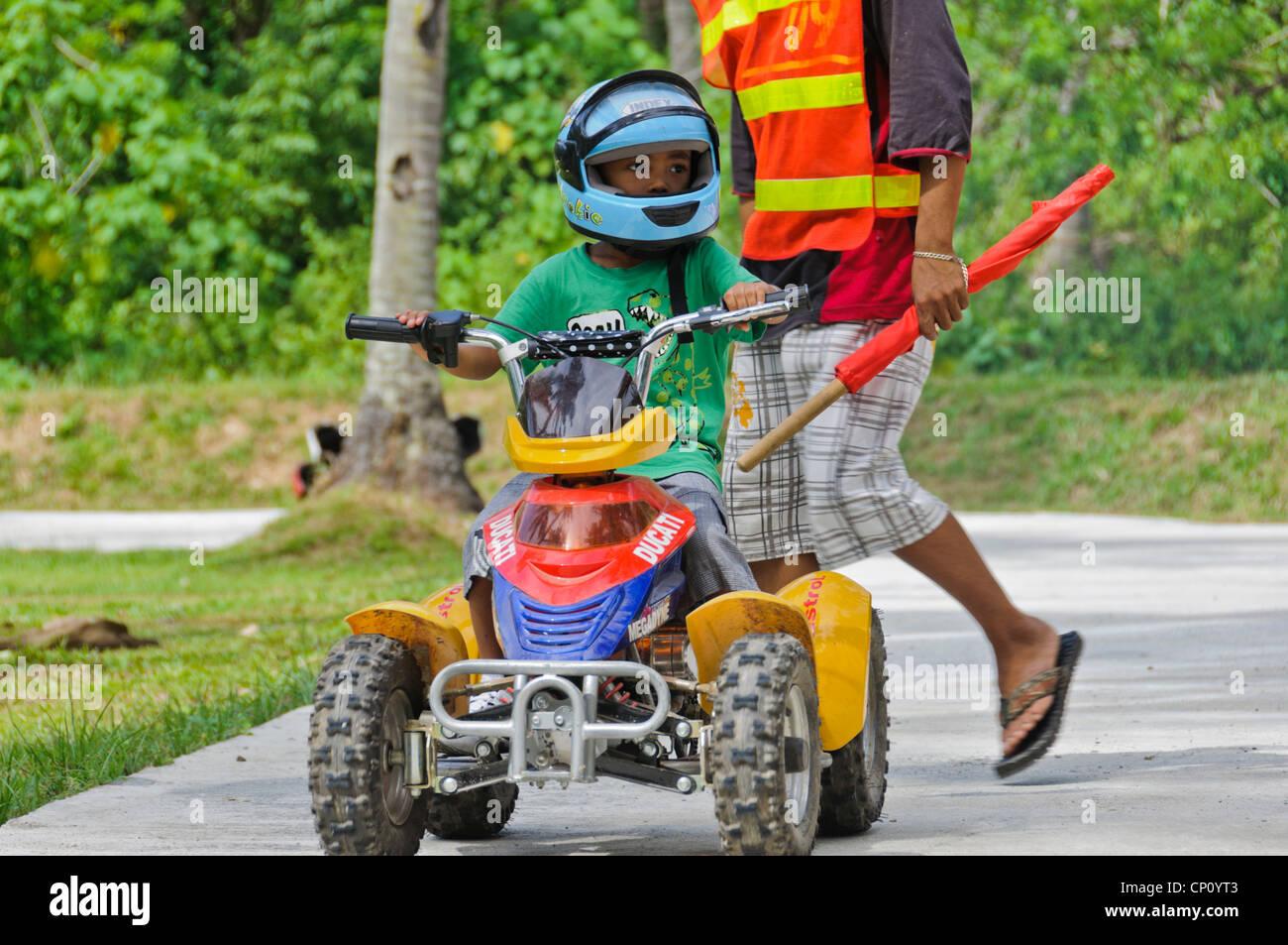 Petit Garçon Asiatique Avec De Grands Enfants équitation Casque Quad