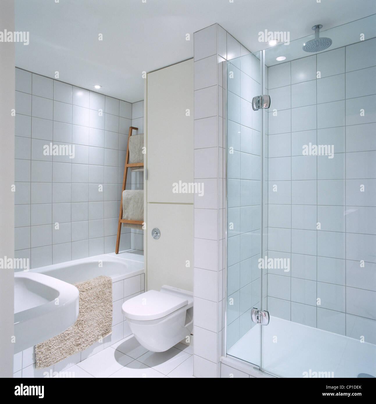 Une salle de bains moderne avec des murs blancs et de carrelage en ...