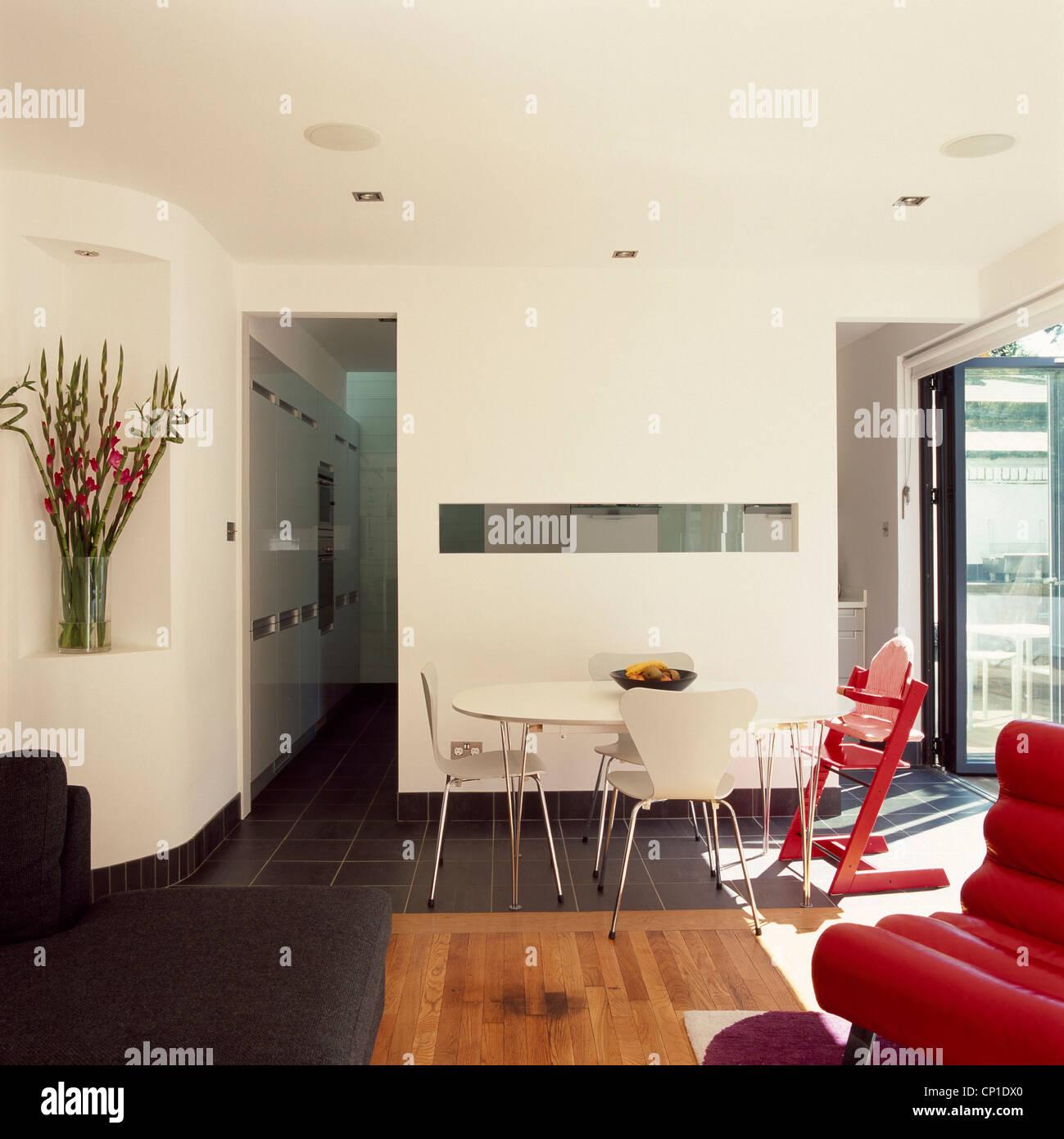 Une salle à manger moderne avec une table ronde et chaises à côté d ...