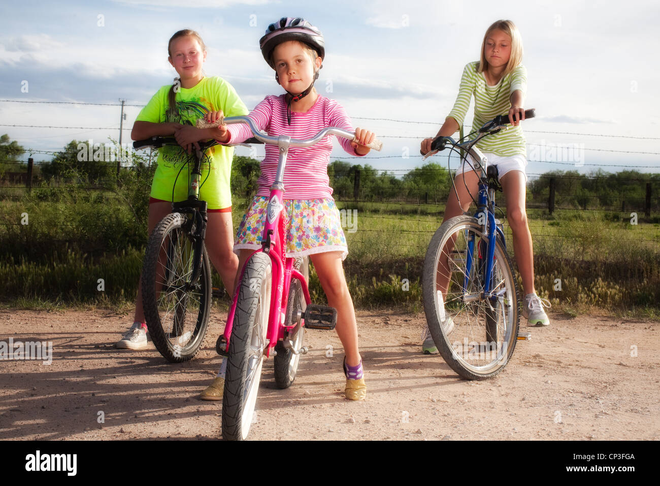 Trois filles sur une bicyclette en zone rurale. Photo Stock