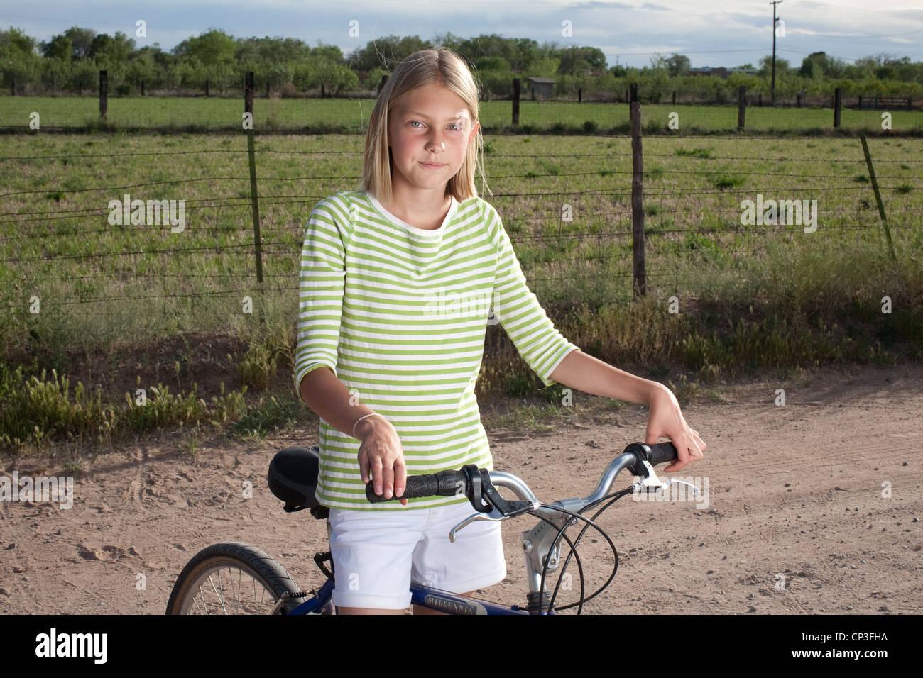 Onze ans, fille, et être prêt à monter son vélo dans une zone rurale. Photo Stock