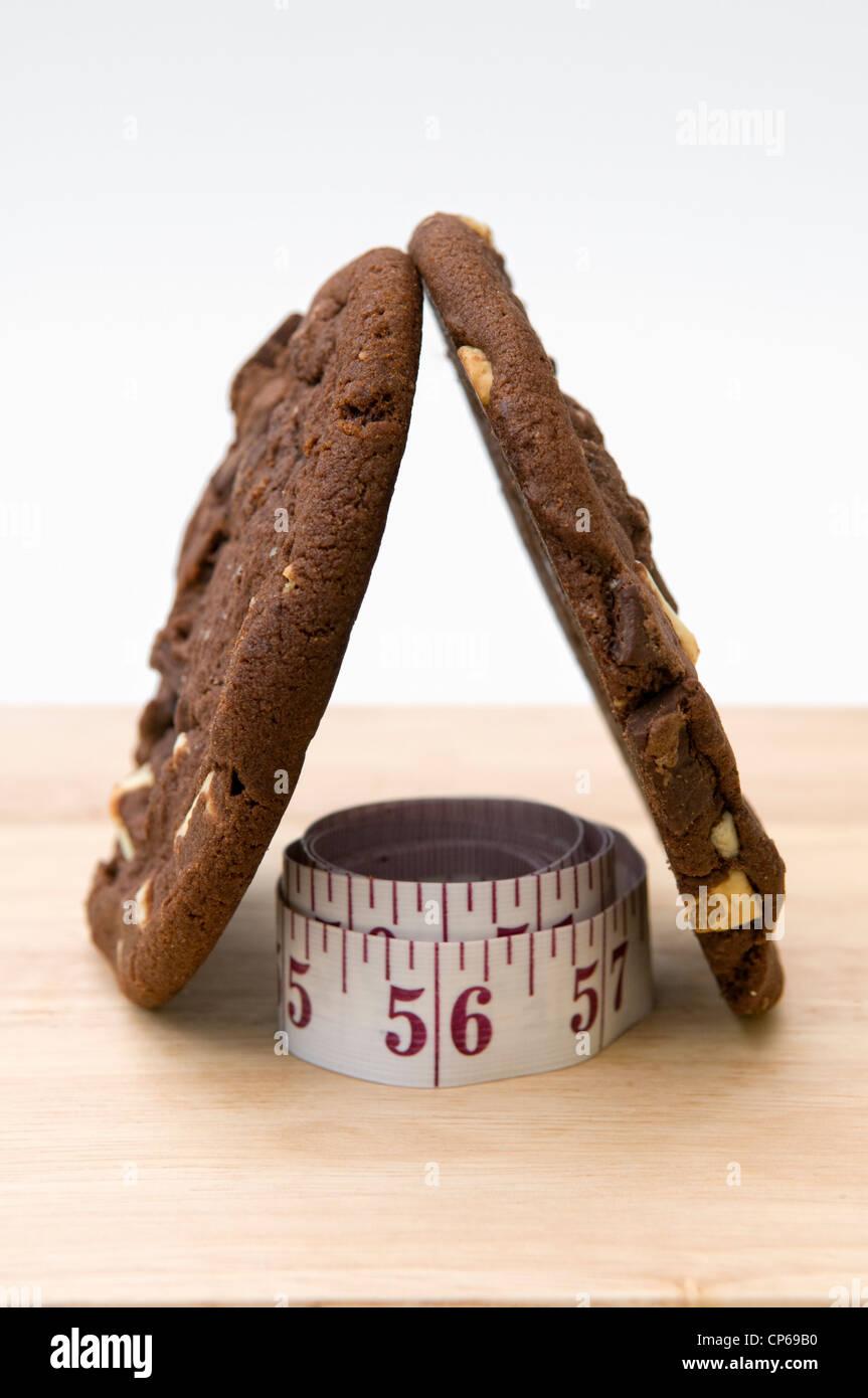 Cookies sur planche à hacher avec ruban de mesure représentant concept que manger des biscuits sera pile Photo Stock