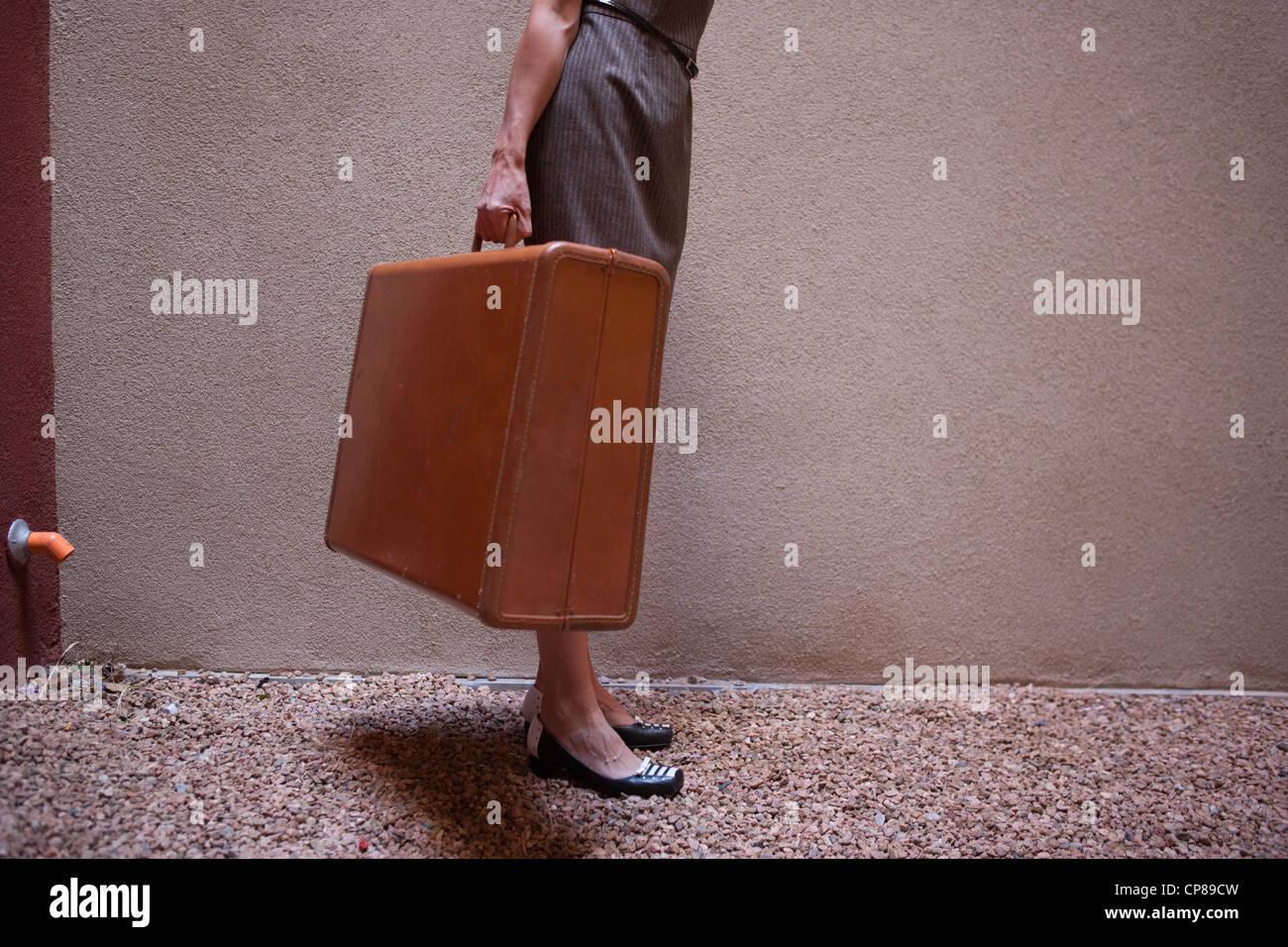 Femme portant une valise vintage. Photo Stock