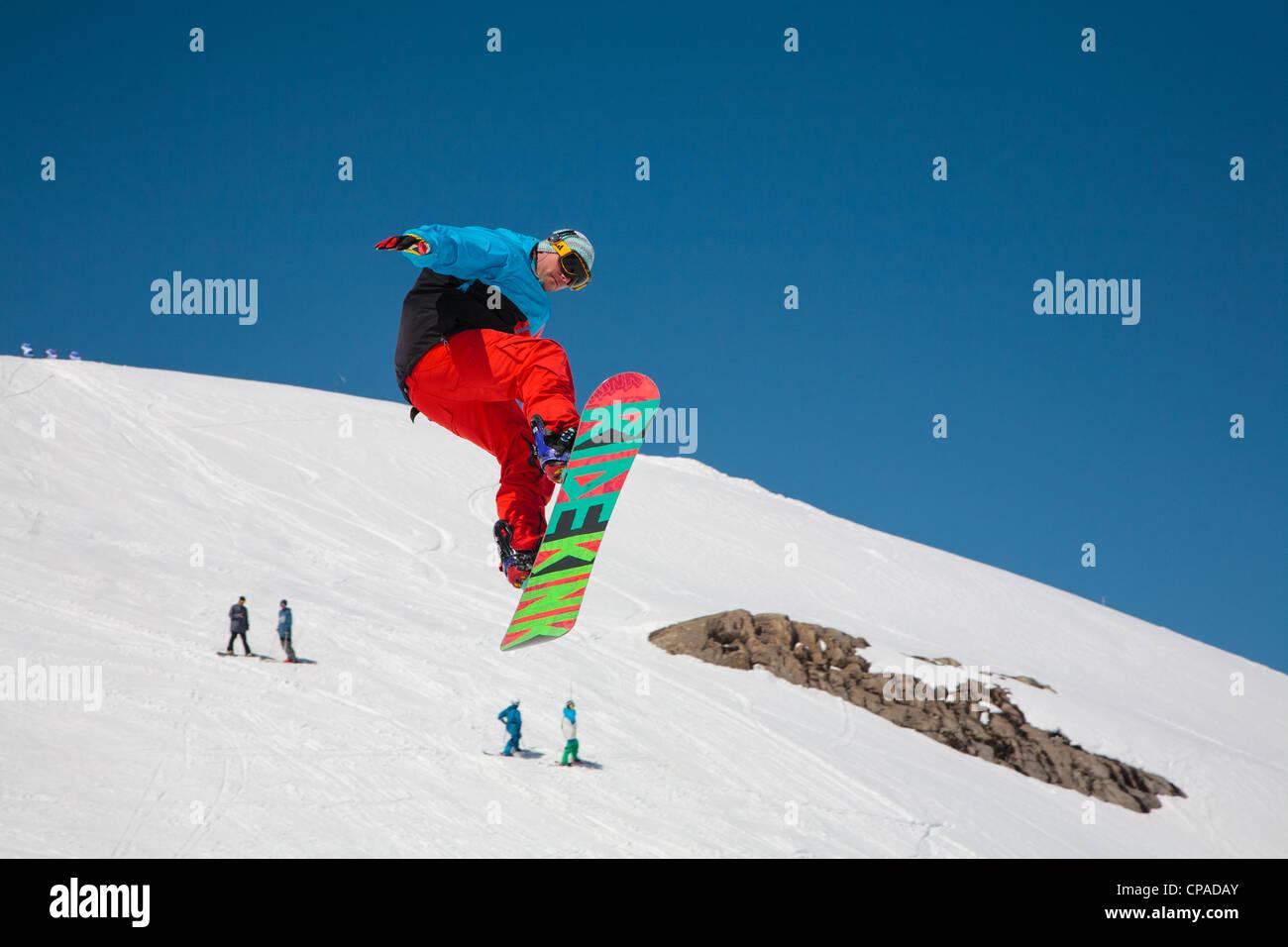 Un free-style boarder exécute un saut et une torsion contre un fond de neige. 1 de 2. Photo Stock