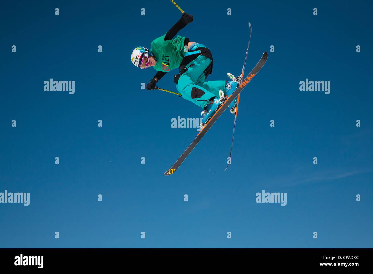 Un skieur de style libre exécute un saut et twist contre un ciel bleu clair. 4 de 4. Photo Stock
