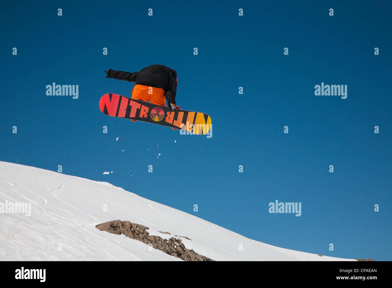 Un free-style boarder exécute un saut et twist contre un ciel bleu clair. 1 de 3. Photo Stock