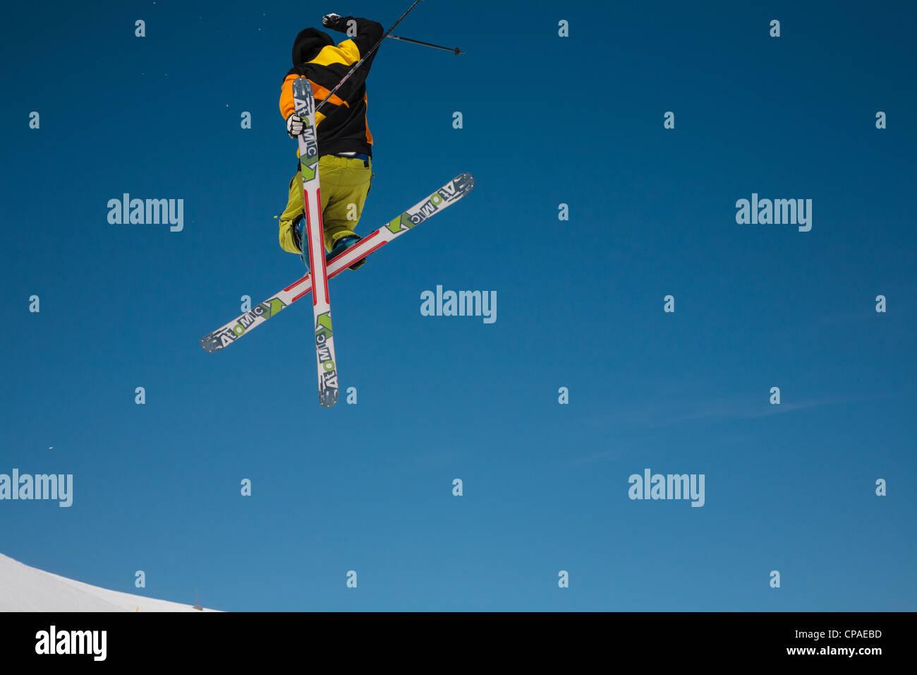 Un skieur de style libre exécute un saut et twist contre un ciel bleu clair. 1 de 2. Photo Stock