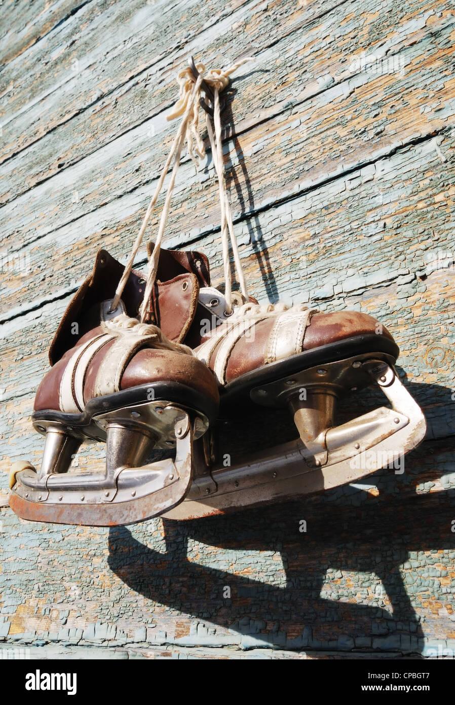 Vintage paire de patins à glace mens accrochée à un mur en bois Photo Stock