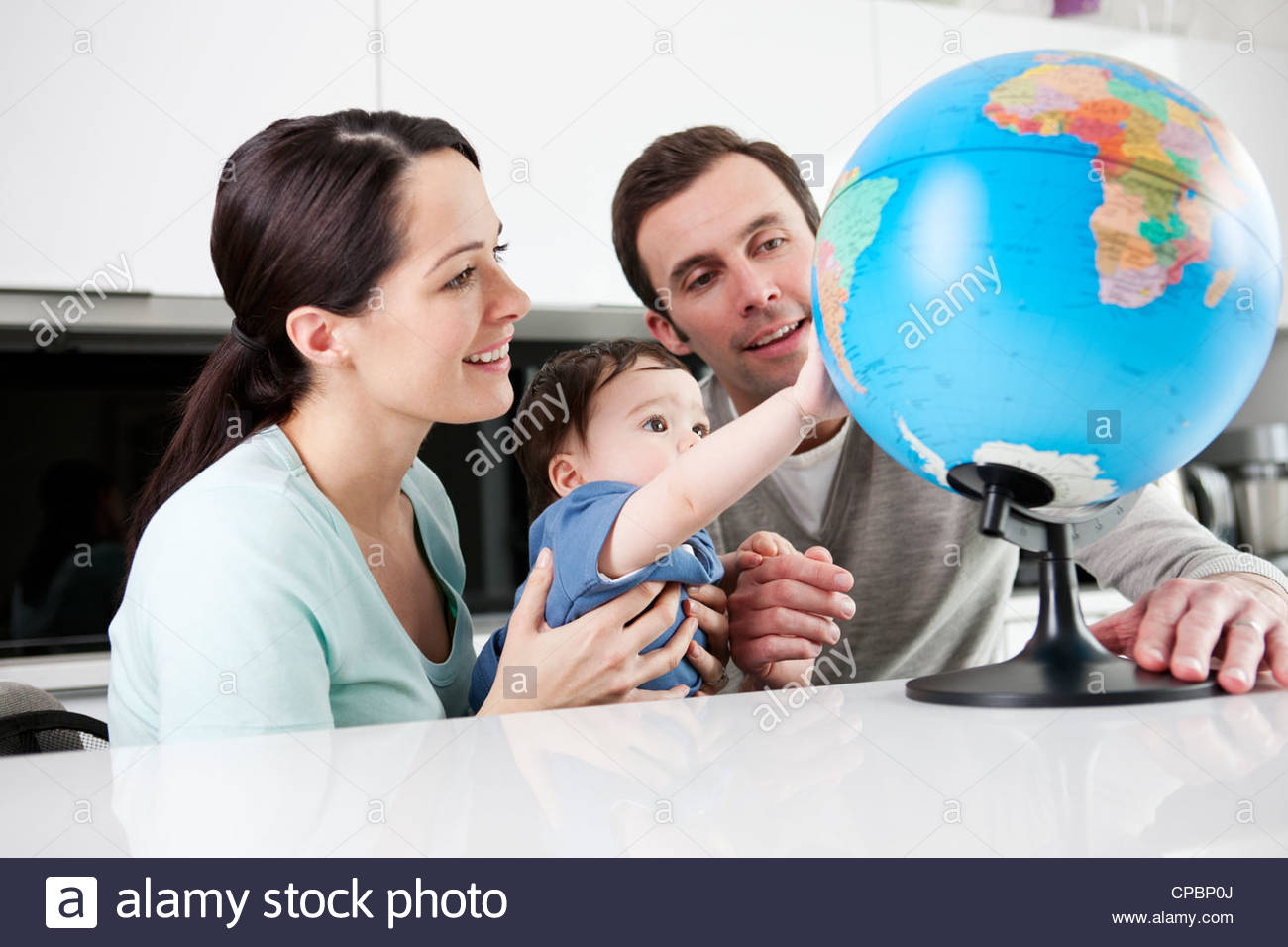Un couple et leur fils bébé looking at a globe Photo Stock