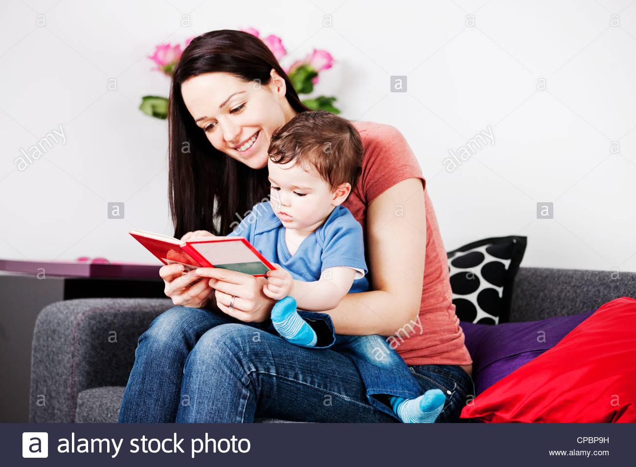 Une mère et son bébé assis sur le canapé en lisant un livre Photo Stock