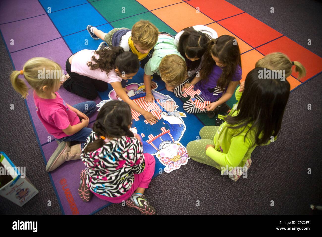 Sur un sol de la classe, un groupe d'enfants de maternelle collaborer pour assembler un puzzle à San Clemente, Photo Stock